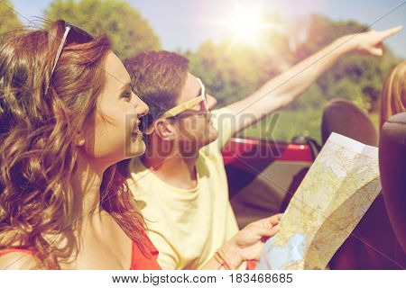 leisure, road trip, travel and people concept - happy friends with map driving in cabriolet car at country and pointing finger to something ahead