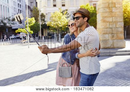 Couple using selfie stick in city smiling