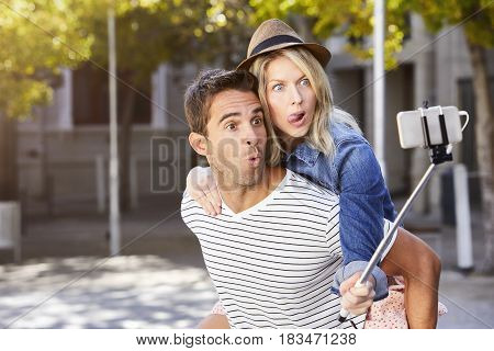 Couple messing about for selfie in city