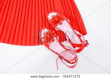 Red pleated skirt with floral red shoes isolated