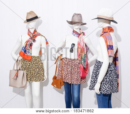 female clothing with hat and bag ,jeans on three mannequin-wooden background