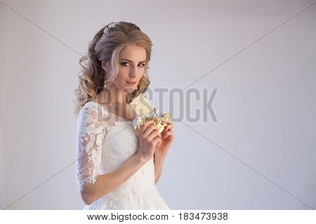 bride in wedding dress holding a chocolate in the hands