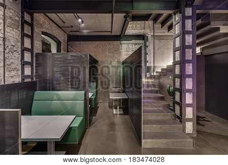 Loft style cafe with brick and concrete walls, column, stairway with reticulated partition and glowing lamps. There are green sofas with gray tables and partitions, small table with chair, big cactus.