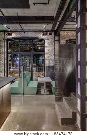 Interior in a loft style in a cafe with brick and concrete walls, glowing lamps. There is a bar rack, stairway, green sofas with tables and partitions on the large window background. Vertical.