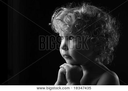 Молиться маленькая девочка, изолированные на черном фоне