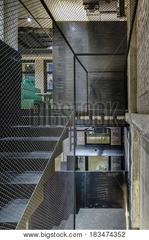 Stairway with reticulated partitions in a cafe in a loft style with brick and concrete walls. There are green sofas with tables, glowing lamps, dark partitions. Vertical.