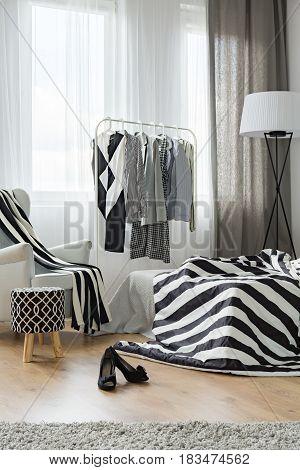 Female clothes on hanger in modern bedroom