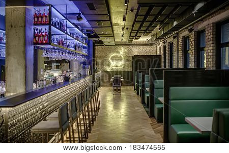 Stylish glowing cafe in a loft style with brick walls and concrete column. There is a bar rack with chairs, shelves with bottles and glasses, bar equipment, sofas with tables, luminous burger on wall.
