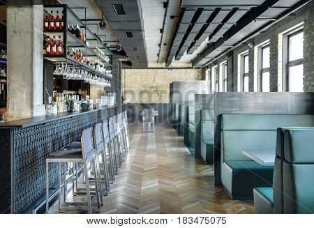 Stylish restaurant in a loft style with brick walls and a concrete column. There is a textured bar rack with chairs, shelves with bottles and glasses, bar equipment, sofas with tables and partitions.