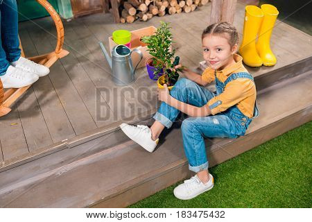 High Angle View Of Adorable Little Girl Sitting On Porch And Cultivating Green Plant In Pot