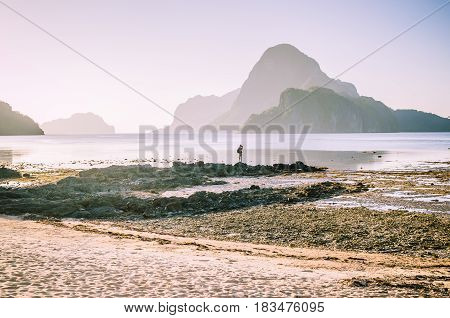 Lonely photographer on top of the rocks during low tide making photo on morning sunrise light in front of amazing Cadlao Island, El-Nido, Palawan, Philippines.