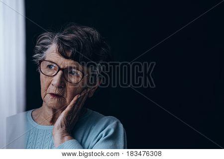 Old Woman In Dark Room