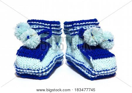 Baby clothes. Blue booties with handmade pom-poms.