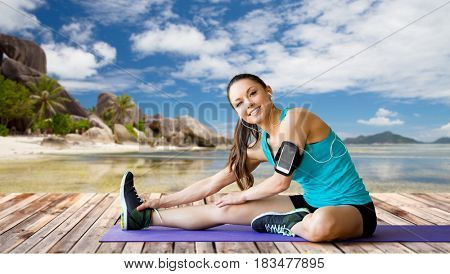 fitness, sport, exercising, technology and people concept - smiling woman wearing armband with smartphone and earphones stretching leg on mat over exotic tropical beach background