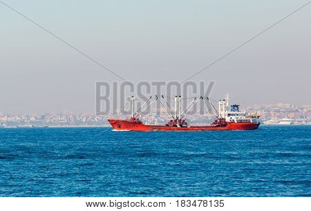 Large cargo ship proceeding along the Bosphorus Channel on the background of the coast on the background