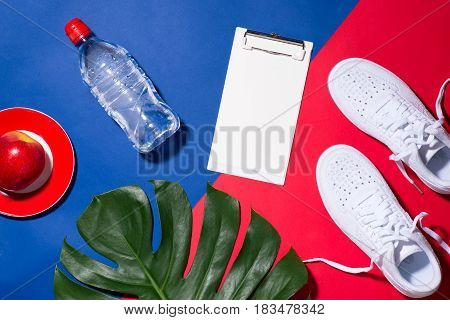 Sport concept. Fitness equipment. Sneakers water apple dumbbell on colorful background.