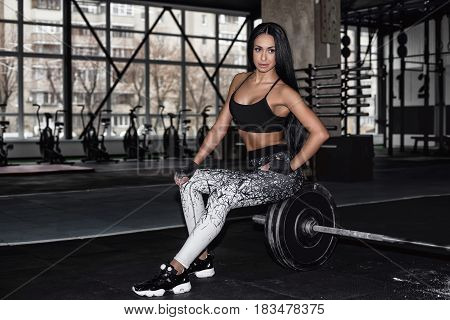 Attractive athletic girl rests after a hard workout in the gym. A sports girl sits and rests after strength training with a barbell. Concept: power strength healthy lifestyle sport.
