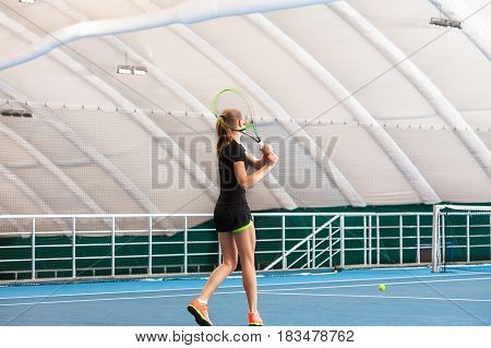 The young girl in a closed tennis court with ball and racket