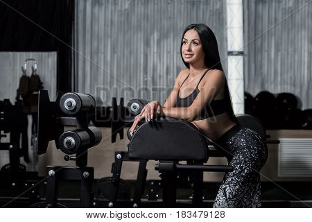 Concept: power strength healthy lifestyle sport. Powerful attractive muscular girl engaged in fitness. Athlete resting after a hard workout.