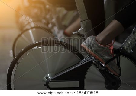 Girl doing sport biking in the gym for fitness/ cinematic tone / Made from light photo graphic / soft focus