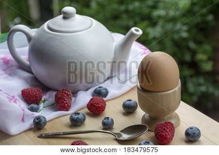One brown egg, teakettle, spoon and berries on the wooden table with green leaves as background