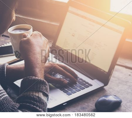 Cropped image of a young man working on his laptop in a coffee shop, rear view of business man hands busy using laptop at office desk,young male student typing on computer sitting at wooden table