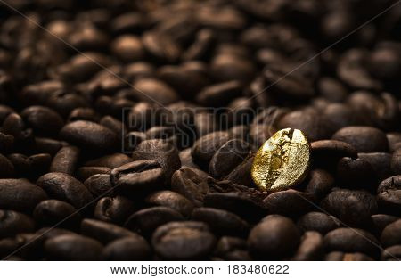 Individuality standing out from a crowd concept close up of a single bright gold coffee bean over many dark ones with copy space