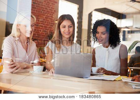 Three Businesswomen Meet In Coffee Shop Shot Through Window