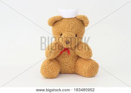 Teddy bear wearing a nurse hat on a white background.