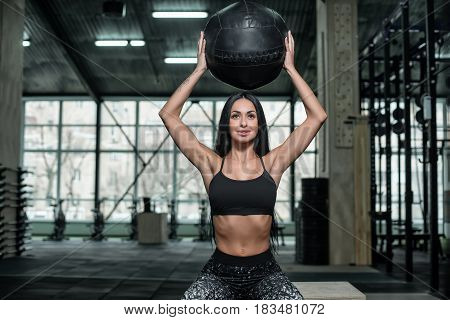Athletic attractive girl posing with a heavy ball for a fitness. Athlete holds the ball over his head. Concept: power strength healthy lifestyle sport.
