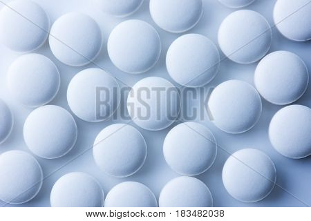 White medicine tablets or  pharmaceutical pills shot from above. Intentionally shot in surreal bluish tone.