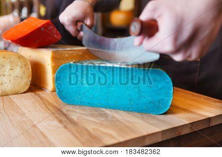 Cutting gouda pesto lavender, blue cheese in grocery shop, closeup