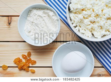 Making of russian style breakfast syrniki or cottage cheese pancakes ingredients on wooden table.