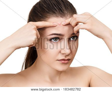 Young girl squeezes pimple on forehead over white background.