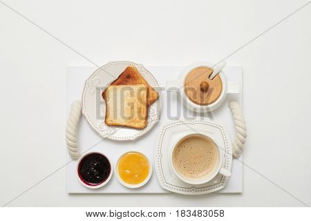 Flay lay of toasts with jams and coffee served on service tray isolated white background
