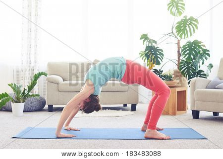 Wide shot of active girl in sportswear doing backbend sequence pose with copy space