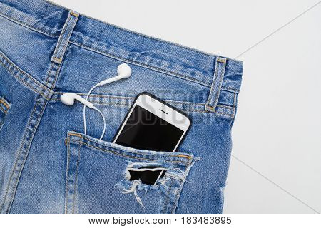 Top view of ripped denim shorts with telephone and headphones in the pocket. Summer vacation items