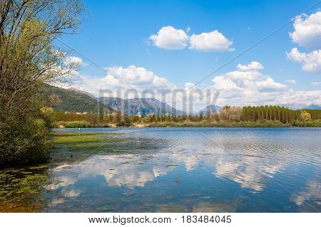 Landscape With Man Fishing From The Shore Of Lake .