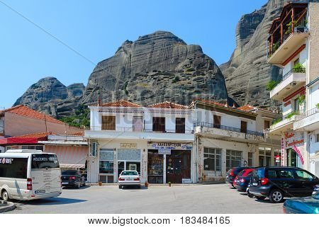 KALAMBAKA GREECE - AUGUST 11 2014: Cars and excursion bus on street of picturesque village of Kalambaka Meteors Greece