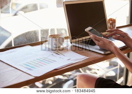 Close Up Of Businesswoman Working In Coffee Shop Using Phone