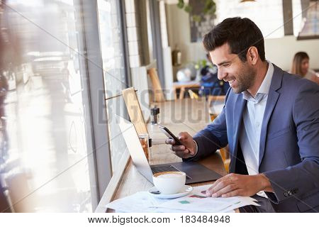 Businessman Using Phone Whilst Working In Coffee Shop