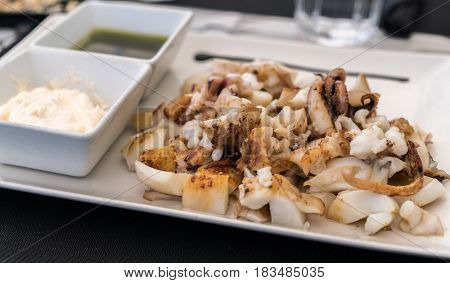 Grilled squid, grilled cuttlefish served as a Spanish tapa with garlic oil and a chopped garlic and parsley, sepia plancha