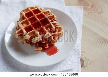 Waffles With Honey, Jam, And Berries On A White Plate, In Close Up View
