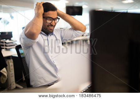 Tensed businessman clenching teeth while sitting in office