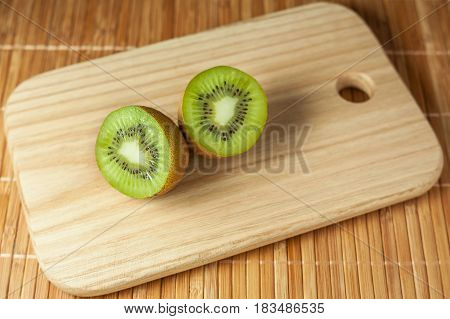 Healthy food. Tropical fruit. Whole and sliced kiwi. Kiwi fruit. Still life. Juicy kiwi on the wooden table