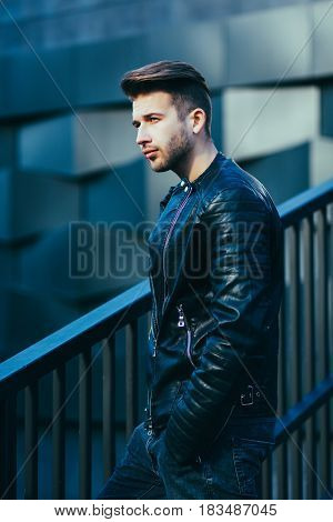 Attractive young male model posing in leather jacket. Fashion photo