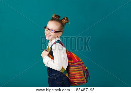 Funny Smiling Little Girl With Big Backpack Jumping And Having Fun Against Blue Wall. Looking At Cam