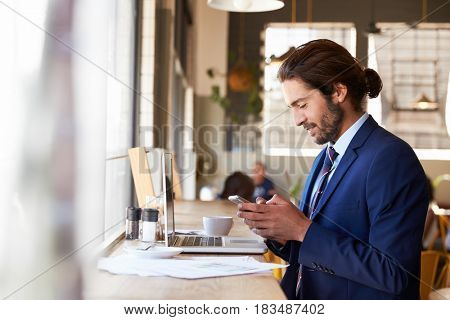 Businessman Using Mobile Phone Whilst Working In Coffee Shop