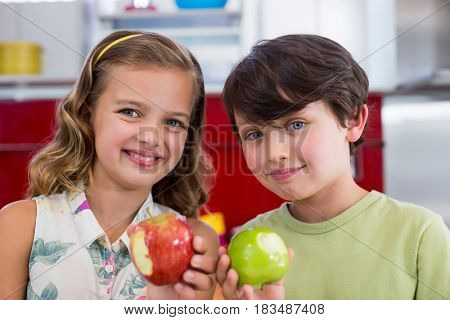 Portrait of siblings showing missing bite of apple in kitchen at home