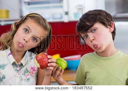 Siblings holding apple and pulling funny faces in kitchen at home